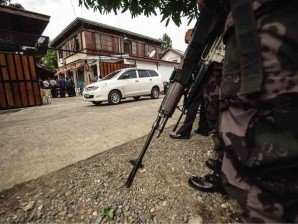 A HEAVILY armed police officer stands guard at the house of an Abra political candidate in January, when political families volunteered to surrender or to have police muzzle their licensed weapons to prevent violence during the midterm election campaign. RICHARD BALONGLONG/INQUIRER NORTHERN LUZON