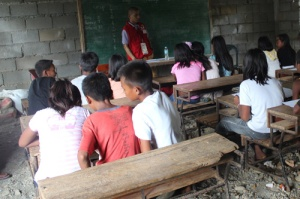 DSWD's Jomel Anthony Gutierrez, a former ABS-CBN Europe correspondent, join pupils in a classroom in Tineg, Abra