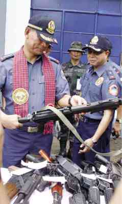SAFEKEEPING PNP Chief Director General Ricardo Marquez inspects one of the high powered firearms surrendered for safekeeping in Abra province. LEONCIO BALBIN JR.